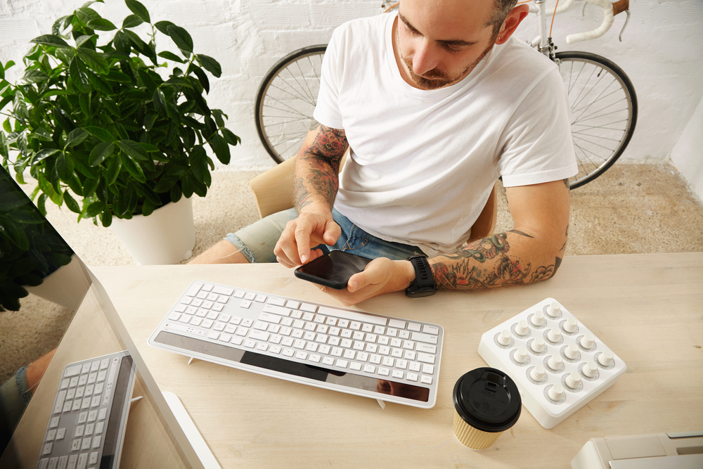 Young tattooed freelancer in blank white t-shirt uses his mobile phone near his computer at home in front of brick wall and parked vintage bike, summer time, top view